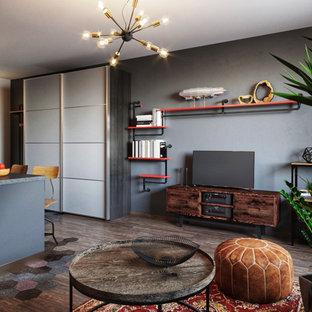 Inredning av ett industriellt litet allrum med öppen planlösning, med grå väggar, laminatgolv och en fristående TV