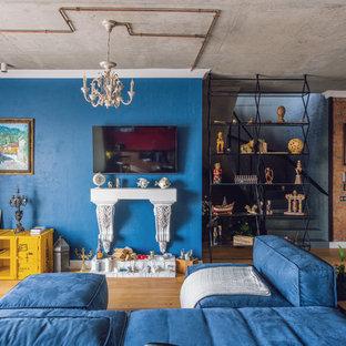 На фото: открытые гостиные комнаты в стиле лофт с паркетным полом среднего тона, коричневым полом, синими стенами и телевизором на стене
