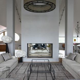 Bild på ett mycket stort industriellt allrum med öppen planlösning, med ett finrum, grå väggar, en dubbelsidig öppen spis, en spiselkrans i betong, heltäckningsmatta och grått golv
