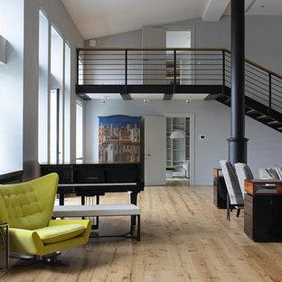 Новый формат декора квартиры: огромная открытая гостиная комната в современном стиле с музыкальной комнатой, серыми стенами и светлым паркетным полом