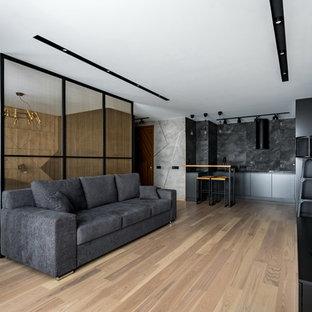 На фото: открытая гостиная комната в современном стиле с светлым паркетным полом, бежевым полом и телевизором на стене без камина с