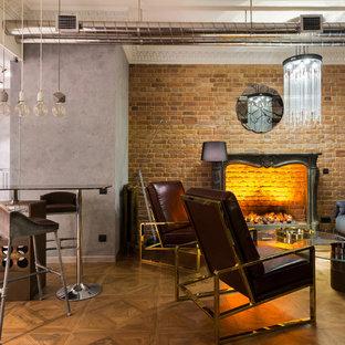 На фото: открытая гостиная комната в стиле лофт с паркетным полом среднего тона, коричневым полом и серыми стенами