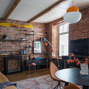 Стильный дизайн: гостиная комната в стиле фьюжн с коричневыми стенами, отдельно стоящим ТВ, балками на потолке, кирпичными стенами и правильным освещением - последний тренд