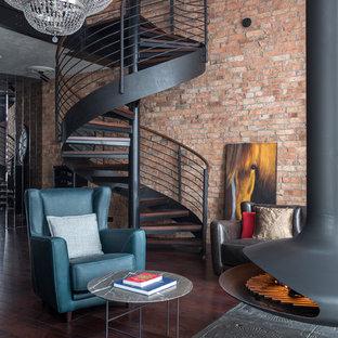 Foto de salón abierto, urbano, con suelo de madera oscura, chimeneas suspendidas, marco de chimenea de metal, suelo marrón y paredes marrones