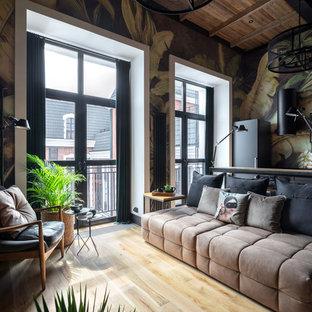 На фото: маленькая открытая гостиная комната в стиле лофт с разноцветными стенами, бежевым полом, светлым паркетным полом и диваном у окна