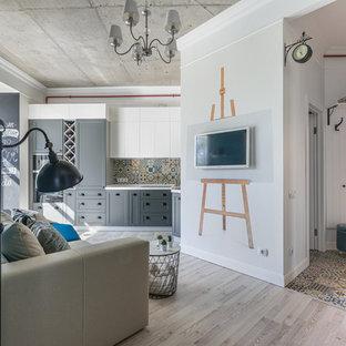 Exempel på ett litet modernt allrum med öppen planlösning, med laminatgolv, en väggmonterad TV, grått golv och vita väggar
