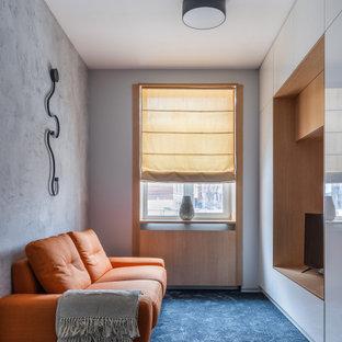 На фото: маленькая гостиная комната в современном стиле с серыми стенами, ковровым покрытием, отдельно стоящим ТВ и синим полом