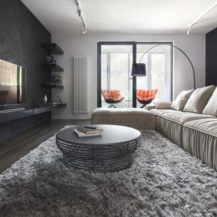 На фото: большая изолированная гостиная комната в современном стиле с черными стенами, паркетным полом среднего тона, телевизором на стене и коричневым полом