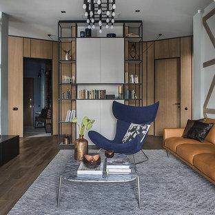 Идея дизайна: изолированная гостиная комната в стиле лофт с паркетным полом среднего тона, коричневым полом и белыми стенами