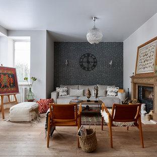 Идея дизайна: открытая гостиная комната в стиле фьюжн с паркетным полом среднего тона, стандартным камином, коричневым полом, черными стенами и фасадом камина из кирпича без ТВ
