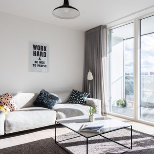 Design ideas for a contemporary open plan living room in London with white walls, light hardwood flooring and beige floors.