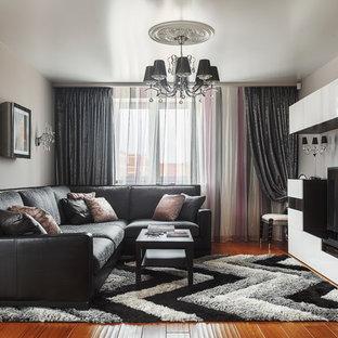 Ejemplo de salón para visitas abierto, actual, de tamaño medio, sin chimenea, con suelo de madera en tonos medios, televisor independiente, paredes grises y suelo naranja