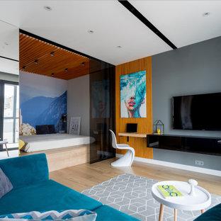 Пример оригинального дизайна: маленькая гостиная комната в современном стиле с серыми стенами, паркетным полом среднего тона, телевизором на стене и коричневым полом