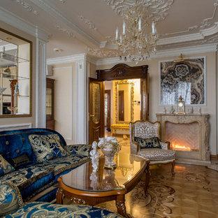 Неиссякаемый источник вдохновения для домашнего уюта: парадная, изолированная гостиная комната в классическом стиле с телевизором на стене, бежевыми стенами, светлым паркетным полом и горизонтальным камином