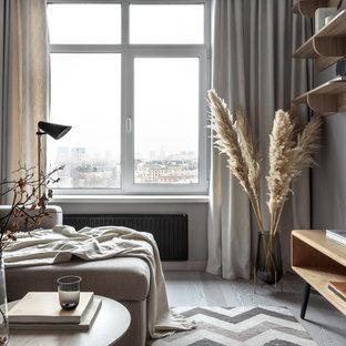 На фото: гостиная комната среднего размера в скандинавском стиле с серыми стенами, светлым паркетным полом, телевизором на стене и серым полом