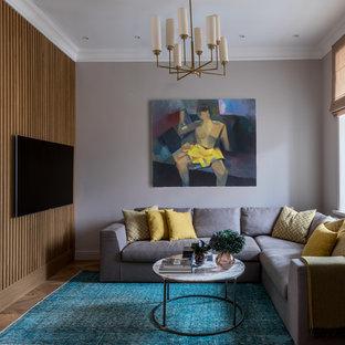 Новый формат декора квартиры: открытая гостиная комната среднего размера в стиле современная классика с серыми стенами, паркетным полом среднего тона, телевизором на стене и коричневым полом без камина