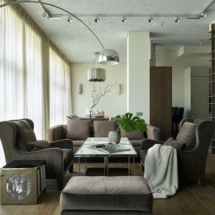 На фото: открытые гостиные комнаты в современном стиле с библиотекой, белыми стенами, темным паркетным полом и коричневым полом