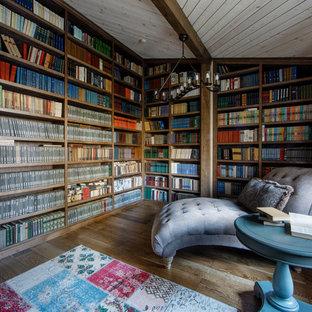 Новый формат декора квартиры: гостиная комната в стиле фьюжн с библиотекой, коричневыми стенами и паркетным полом среднего тона