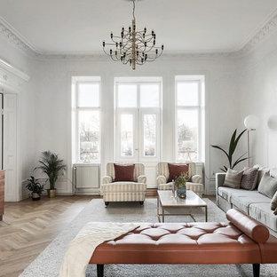 Пример оригинального дизайна: гостиная комната в стиле современная классика с белыми стенами, светлым паркетным полом, телевизором на стене и коричневым полом