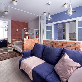 Новые идеи обустройства дома: маленькая открытая гостиная комната в современном стиле с синими стенами, полом из винила, телевизором на стене и бежевым полом без камина