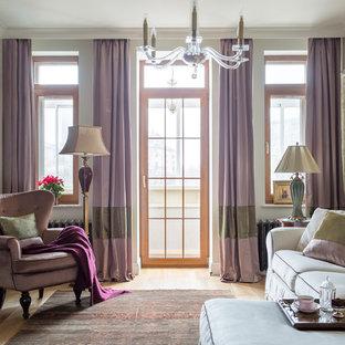 Пример оригинального дизайна интерьера: маленькая изолированная гостиная комната в викторианском стиле с библиотекой, телевизором на стене, бежевыми стенами, светлым паркетным полом и бежевым полом