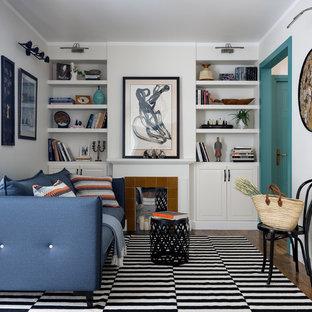 Новые идеи обустройства дома: изолированная гостиная комната в стиле современная классика с библиотекой, бежевыми стенами, темным паркетным полом, камином и фасадом камина из плитки без ТВ