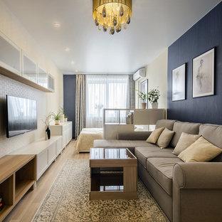Создайте стильный интерьер: изолированная гостиная комната в стиле современная классика с светлым паркетным полом и телевизором на стене - последний тренд