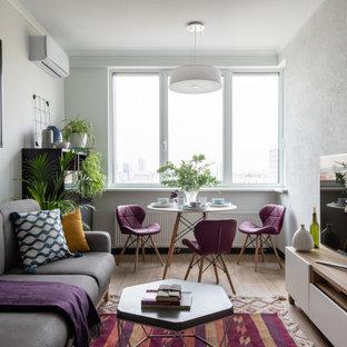 На фото: гостиные комнаты среднего размера в современном стиле с серыми стенами, телевизором на стене и бежевым полом