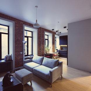 Foto di un soggiorno industriale di medie dimensioni e aperto con pareti grigie, parquet chiaro, nessun camino, parete attrezzata e pavimento beige
