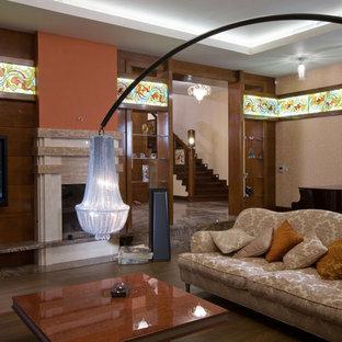 Idéer för ett eklektiskt separat vardagsrum, med orange väggar, mellanmörkt trägolv, en standard öppen spis, en spiselkrans i sten och en väggmonterad TV