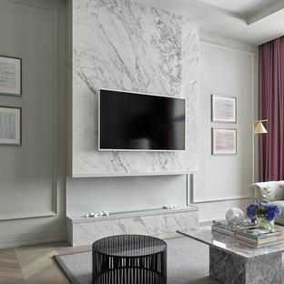 Пример оригинального дизайна интерьера: парадная гостиная комната в стиле современная классика с серыми стенами, светлым паркетным полом, горизонтальным камином, фасадом камина из камня, телевизором на стене и бежевым полом
