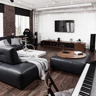 Industriell inredning av ett allrum med öppen planlösning, med ett musikrum, vita väggar, mörkt trägolv, en väggmonterad TV och brunt golv