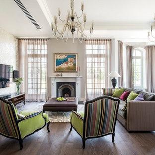 На фото: большая парадная гостиная комната в стиле современная классика с белыми стенами, темным паркетным полом, стандартным камином и телевизором на стене с