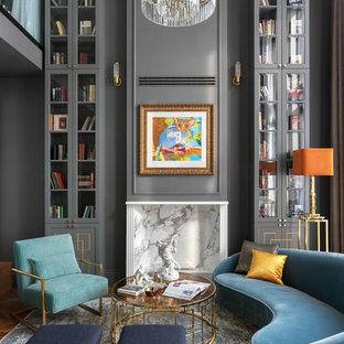Пример оригинального дизайна: открытая гостиная комната в современном стиле с библиотекой, серыми стенами и стандартным камином без ТВ