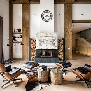 На фото: открытая гостиная комната в современном стиле с белыми стенами, светлым паркетным полом, фасадом камина из камня и стандартным камином без ТВ