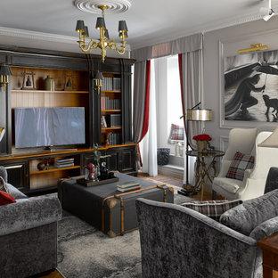 Пример оригинального дизайна: большая гостиная комната в классическом стиле с серыми стенами, паркетным полом среднего тона, коричневым полом и отдельно стоящим ТВ
