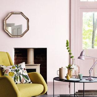 Diseño de salón moderno con paredes rosas, suelo de madera oscura, estufa de leña y suelo negro