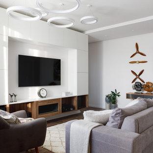 Свежая идея для дизайна: изолированная гостиная комната в современном стиле с белыми стенами, темным паркетным полом, мультимедийным центром и коричневым полом - отличное фото интерьера