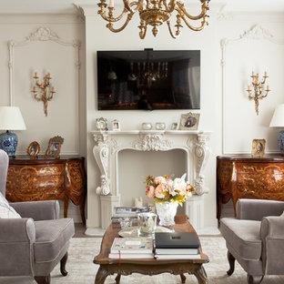 Новый формат декора квартиры: парадная, открытая гостиная комната в викторианском стиле с белыми стенами, телевизором на стене, бежевым полом и паркетным полом среднего тона