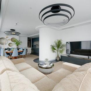 Exempel på ett modernt allrum med öppen planlösning, med vita väggar, ljust trägolv, en fristående TV och beiget golv