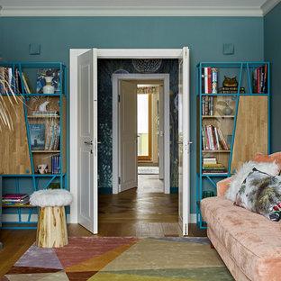 Exemple d'une salle de séjour avec une bibliothèque ou un coin lecture tendance de taille moyenne et fermée avec un mur bleu, un sol en bois brun, aucun téléviseur, un sol marron, une cheminée ribbon et un manteau de cheminée en bois.