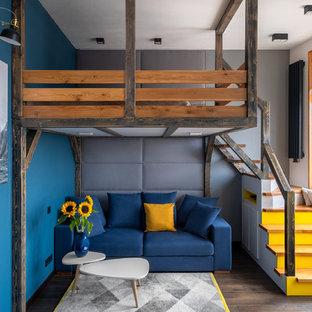 Стильный дизайн: гостиная комната в стиле лофт с синими стенами, темным паркетным полом и коричневым полом - последний тренд