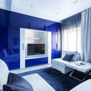 他の地域のコンテンポラリースタイルのおしゃれなファミリールーム (青い壁、壁掛け型テレビ、白い床) の写真