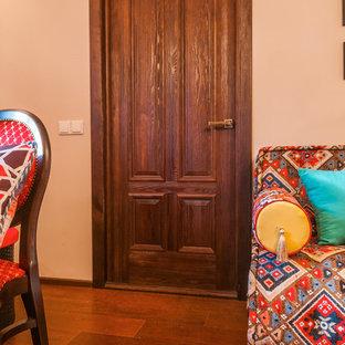 Esempio di un soggiorno etnico di medie dimensioni e chiuso con pareti arancioni, parquet scuro, camino lineare Ribbon, cornice del camino in intonaco e pavimento multicolore