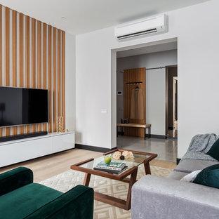 На фото: большая открытая гостиная комната в современном стиле с серыми стенами, светлым паркетным полом, телевизором на стене и бежевым полом с