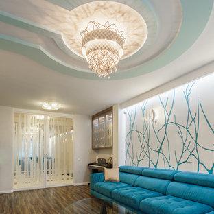 Immagine di un grande soggiorno design aperto con sala della musica, pareti bianche, pavimento in laminato, TV a parete e pavimento marrone