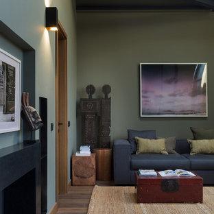 Свежая идея для дизайна: маленькая двухуровневая гостиная комната в современном стиле с зелеными стенами, паркетным полом среднего тона, стандартным камином, фасадом камина из камня и коричневым полом - отличное фото интерьера