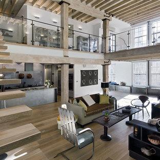 На фото: парадная, открытая гостиная комната в стиле лофт с белыми стенами, светлым паркетным полом и бежевым полом без камина с