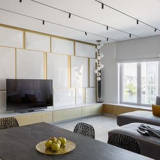 На фото: гостиная комната в современном стиле с белыми стенами, светлым паркетным полом и отдельно стоящим ТВ с