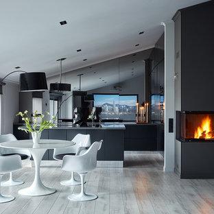 Пример оригинального дизайна интерьера: гостиная-столовая в современном стиле с белыми стенами, светлым паркетным полом, камином и серым полом